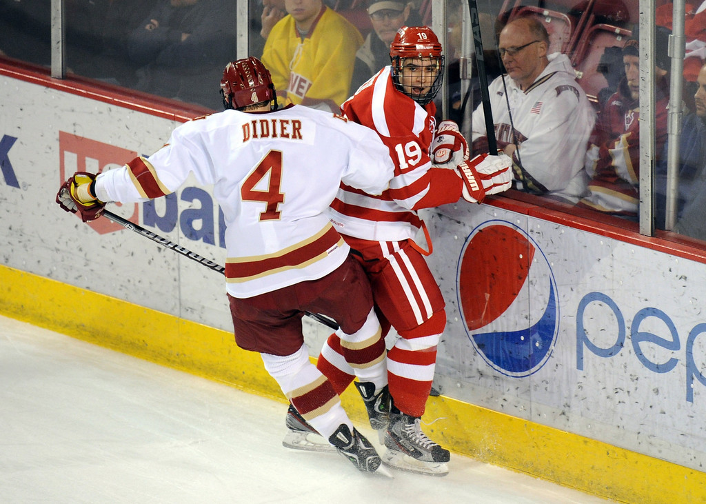 . University of Denver Josiah Didier, left, checks Boston University Matt Nieto in the 1st period of the game at Magness Arena on in Denver on Saturday, Dec. 29, 2012. Hyoung Chang, The Denver Post