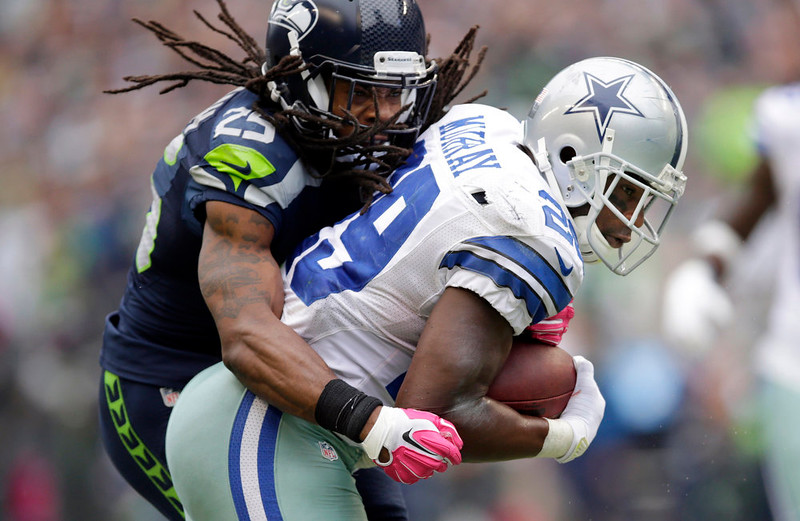 . Dallas Cowboys running back DeMarco Murray, right, powers through a tackle by Seattle Seahawks cornerback Richard Sherman to score a touchdown in the second half of an NFL football game, Sunday, Oct. 12, 2014, in Seattle. (AP Photo/Scott Eklund)