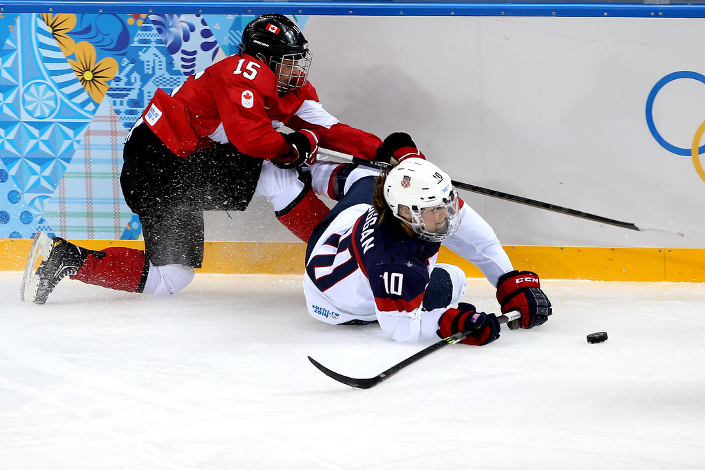 . Melodie Daoust #15 of Canada and Meghan Duggan #10 of the United States fight for a loose puck during the Women\'s Ice Hockey Preliminary Round Group A game on day five of the Sochi 2014 Winter Olympics at Shayba Arena on February 12, 2014 in Sochi, Russia.  (Photo by Bruce Bennett/Getty Images)
