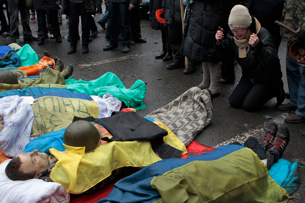 . Activists pay respects to protesters killed in clashes with police, in Kiev\'s Independence Square, the epicenter of the country\'s current unrest, Thursday, Feb. 20, 2014. Fierce clashes between police and protesters, some including gunfire, shattered a brief truce in Ukraine\'s besieged capital, killing numerous people. The deaths came in a new eruption of violence just hours after the country\'s embattled president and the opposition leaders demanding his resignation called for a truce and negotiations to try to resolve Ukraine\'s political crisis. (AP Photo/Sergei Chuzavkov, File)