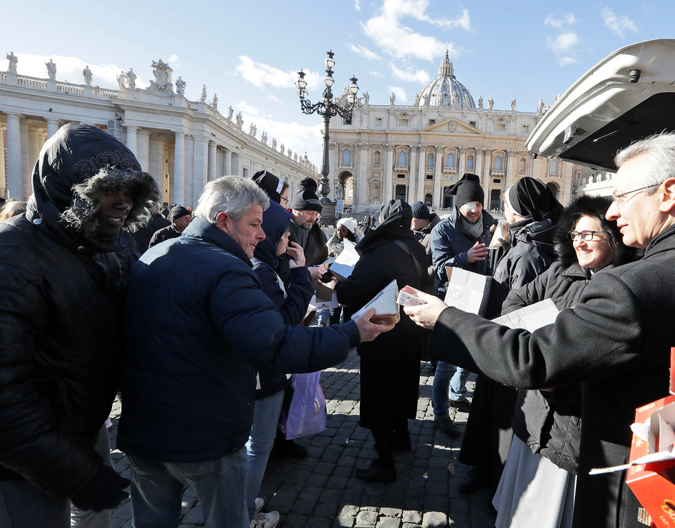 . Nuns distribute food and drinks to needy people in St. Peter\'s square at the Vatican, Friday, Jan. 6, 2017. After the Angelus prayer Pope Francis offered some 300 needy people a simple lunch of a sandwich and drink, as part of his long-running outreach to the poor and homeless who live around the Vatican.(AP Photo/Andrew Medichini)