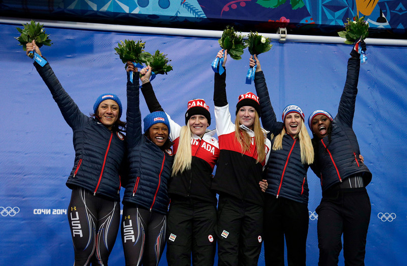 . From left to right, silver medal winners from the United States Elana Meyers and Lauryn Williams, gold medal winners from Canada Kaillie Humphries and Heather Moyse, and bronze medal winners from the United States Jamie Greubel and Aja Evans pose during the flower ceremony during the women\'s bobsled competition at the 2014 Winter Olympics, Wednesday, Feb. 19, 2014, in Krasnaya Polyana, Russia. (AP Photo/Michael Sohn)