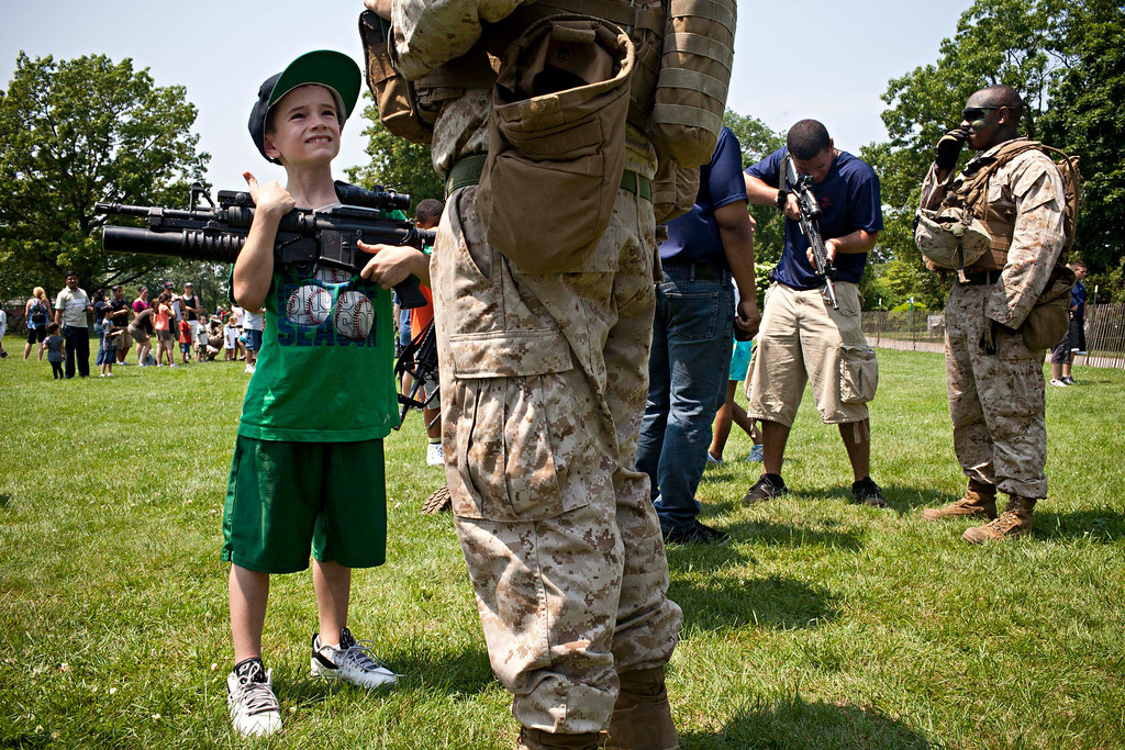 . Connor Kennedy, 7, from Farmingdale, New York, holds the M4 carbine rifle of a marine from 1st Battalion 9th Marines Charlie Company 2nd Platoon during a demonstration put together by the Marines as part of Fleet Week in East Meadow, New York, May 26, 2012. As part of the demonstration, Marines from the 1st Battalion 9th Marines Charlie Company 2nd Platoon flew in a V-22 Osprey from New York to Eisenhower Park in East Meadow, New York and stormed a field, where civilians could watch the demonstration. Marines spoke to civilians after the demonstration and civilians could tour various aircraft, including the V-22 Osprey. REUTERS/Andrew Burton
