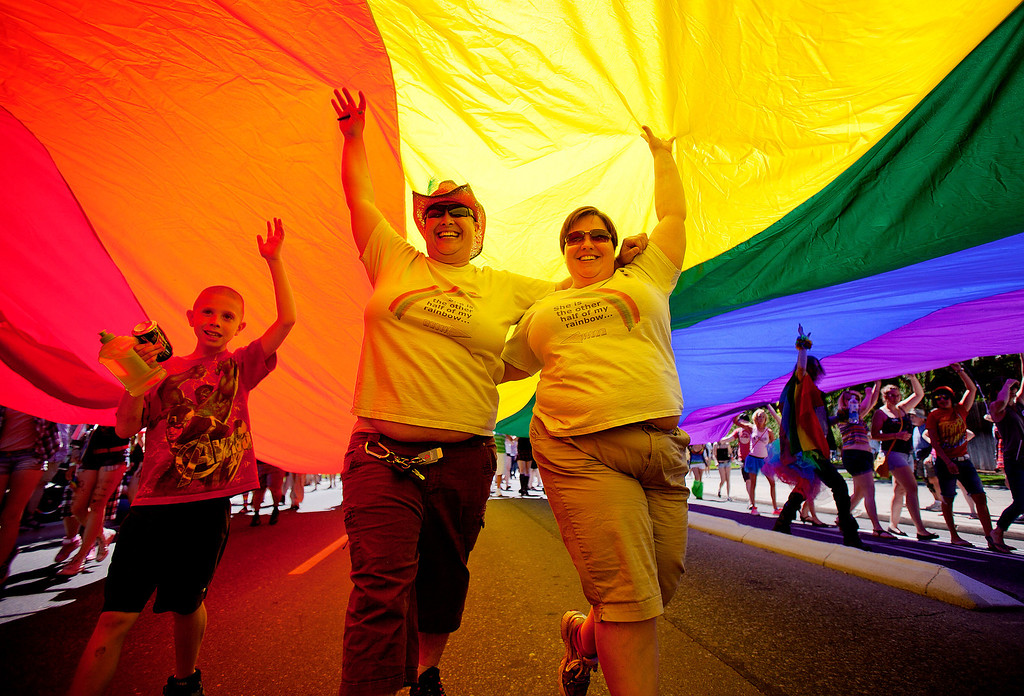 . Leslie Maggard, center left, and partner Kristi Watson, right, help hold up a large rainbow flag while marching down 9th Avenue during the Boise Gay Pride celebration on Saturday, June 15, 2013, in Boise, Idaho. (AP Photo/The Idaho Statesman, Kyle Green)
