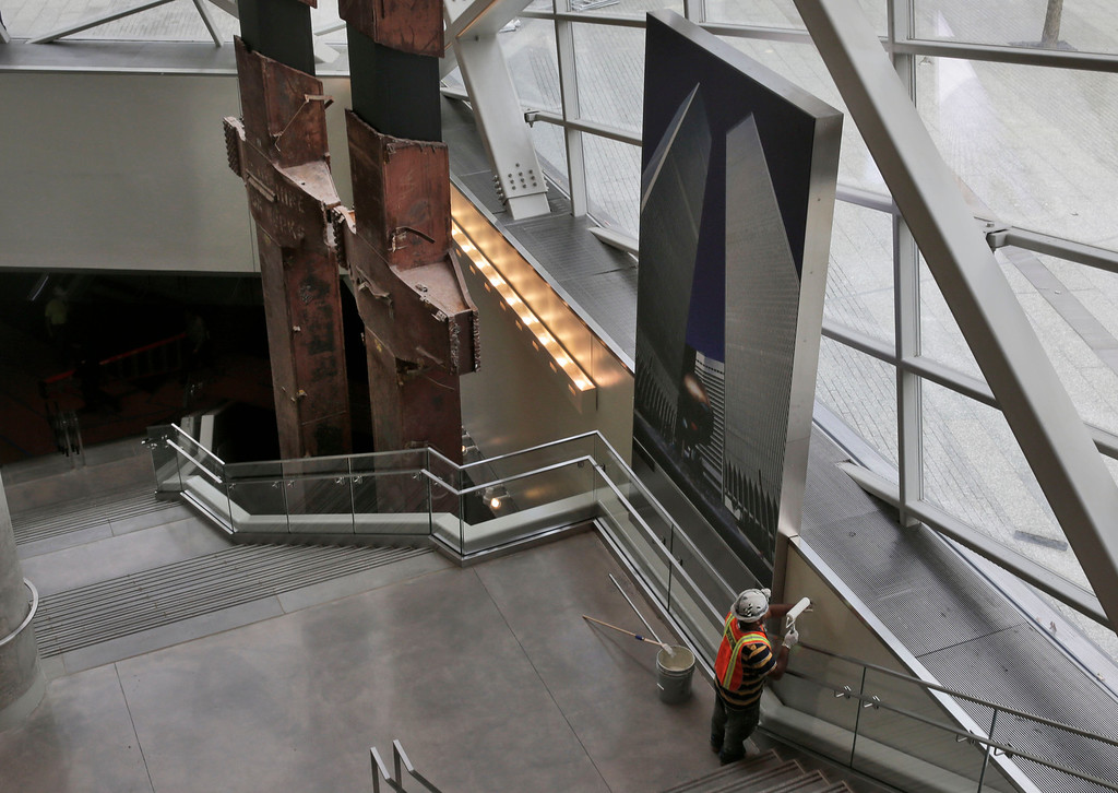 . A painter gives a touch-up to a wall inside the Sept. 11 Museum, adjacent to a pair of World Trade Center tridents, that once formed part of the exterior structural support of the east facade of the building, Wednesday, May 14, 2014, in New York. Leaders of the soon-to-open museum are portraying it as a monument to unity and resilience. (AP Photo)