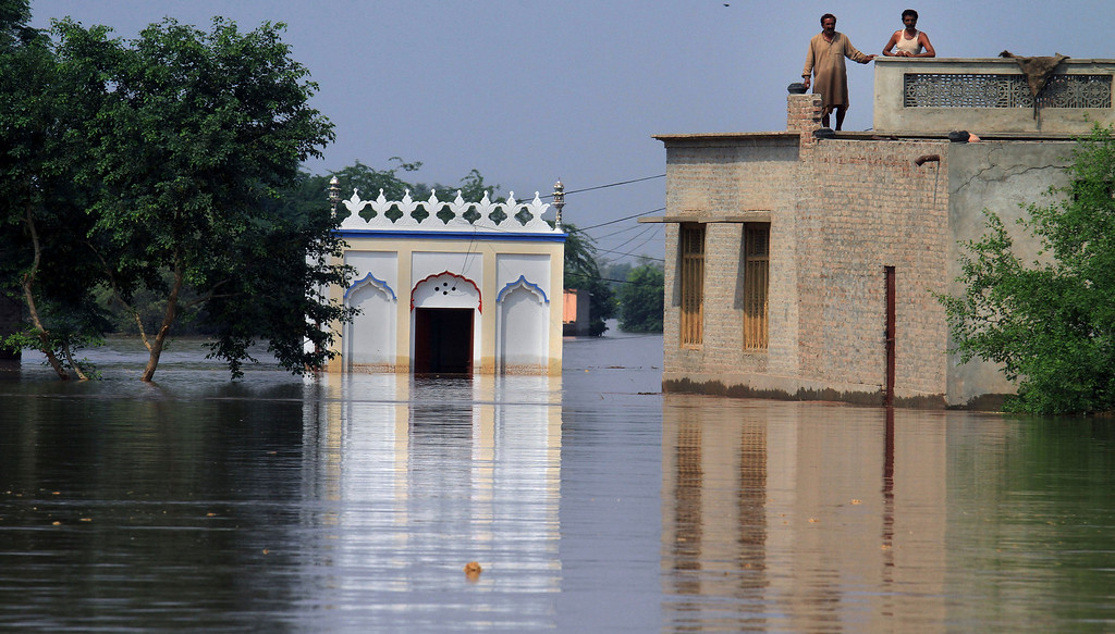 . Two Pakistani villagers wait for help on the rooftop of their house in a flooded suburb of Jhang district, 260 kilometers (161 miles) northwest of Lahore, Pakistan, Wednesday, Sept. 10, 2014.  (AP Photo/K.M. Chaudary)