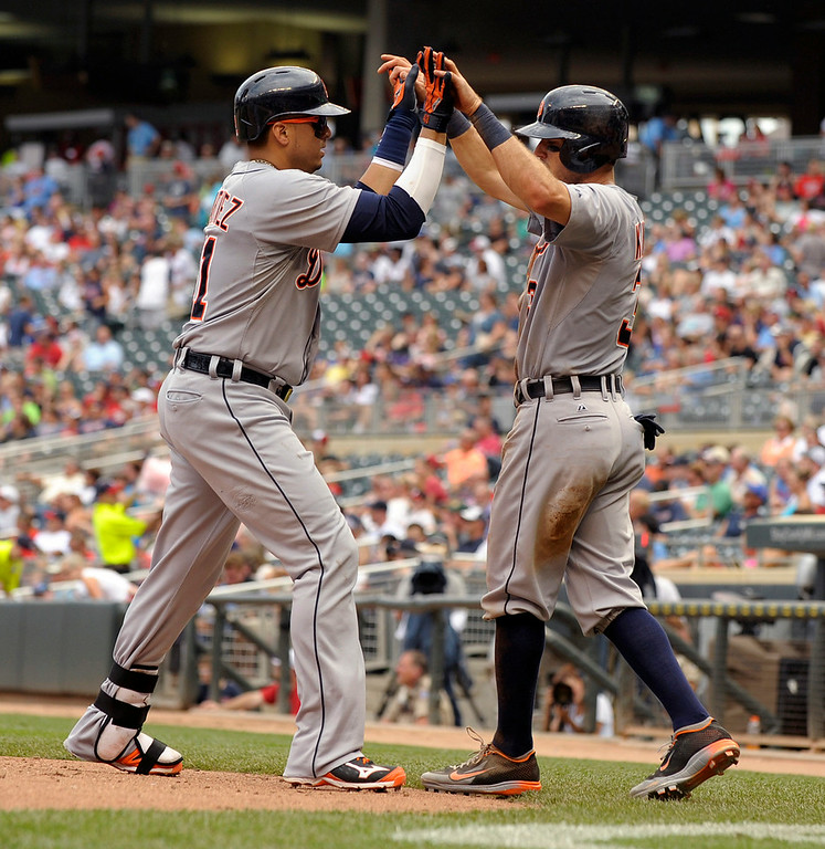 . Detroit Tigers� Ian Kinsler, right, congratulates Victor Martinez, left, after scoring on Martinez two-run home run during the sixth inning of a baseball game against the Minnesota Twins in Minneapolis, Sunday, Aug. 24, 2014. Detroit won 13-4.(AP Photo/Tom Olmscheid)