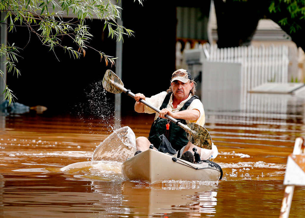 . Michael Williams uses a kayak to retrieve valuables from his mother Karleen Shaw\'s house on Sunday, May 24, 2015 in Lexington Okla.  Williams forced his mother from the house Saturday night after the water level got waist high. (Steve Sisney/The Oklahoman via AP) LOCAL STATIONS OUT (KFOR, KOCO, KWTV, KOKH, KAUT OUT); LOCAL WEBSITES OUT; LOCAL PRINT OUT (EDMOND SUN OUT, OKLAHOMA GAZETTE OUT) TABLOIDS OUT