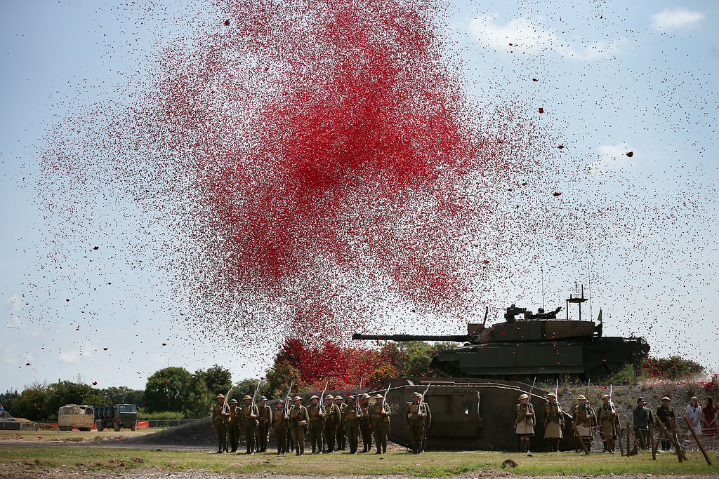 . BOVINGTON, UNITED KINGDOM - AUGUST 04:  Members of living history societies stand under a shower of a million poppy flowers representing the dead during a World War One centenary ceremony at the Tank Museum, Bovington on August 4, 2014 in England. Monday August 4, 2014  marks the 100th anniversary of Great Britain\'s declaration of war on Germany. In 1914 British Prime Minister Herbert Asquith announced at 11 pm that Britain was to enter the war after Germany had violated Belgium neutrality. The First World War or the Great War lasted until 11 November 1918 and is recognised as one of the deadliest historical conflicts with millions of causalities. A series of events commemorating the 100th anniversary are taking place throughout the day.  (Photo by Peter Macdiarmid/Getty Images)