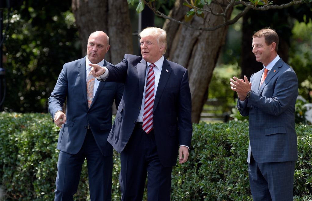 . President Donald Trump walks with Clemson University President Jim Clements, left, and Clemson head football coach Dabo Swinney to the  the South Lawn of the White House in Washington, Monday, June 12, 2017, for a ceremony where the president honored the 2016 NCAA Football National Champions Clemson University Tigers. (AP Photo/Susan Walsh)