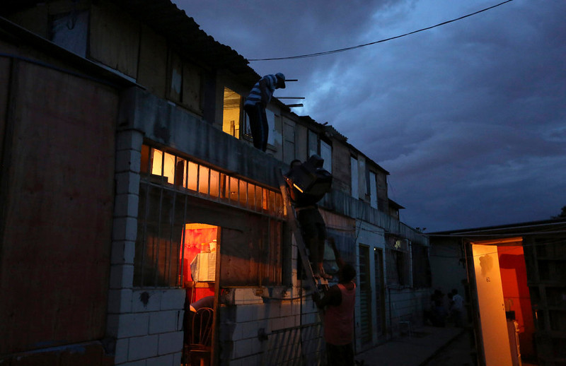 . A man from Brazil\'s Movimento dos Sem-Teto (Roofless Movement) holds a TV, as other men help him climb down a ladder at an area that used to be a nursery and school in Sao Paulo March 10, 2013. More than 1,200 people from Brazil\'s roofless movement live in an explosion prone area that has been contaminated with methane since October 2012, local media reported. According to the Environmental Sanitation Technology Company in the State of Sao Paulo (CETESB) the soil and water from the groundwater are contaminated with methane. Picture taken March 10, 2013. REUTERS/Nacho Doce