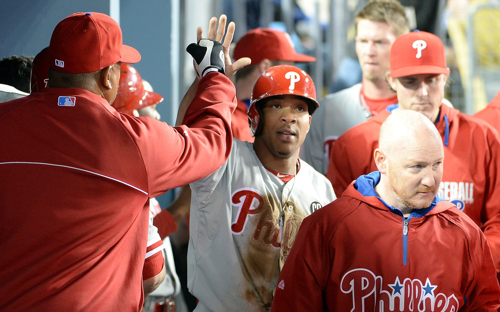 . Philadelphia Phillies\' Ben Revere, center, high fives teammates after scoring on a sac fly ball by Ryan Howard (not pictured) in the fifth inning of a baseball game against the Los Angeles Dodgers on Tuesday, April 22, 2013 in Los Angeles.   (Keith Birmingham/Pasadena Star-News)