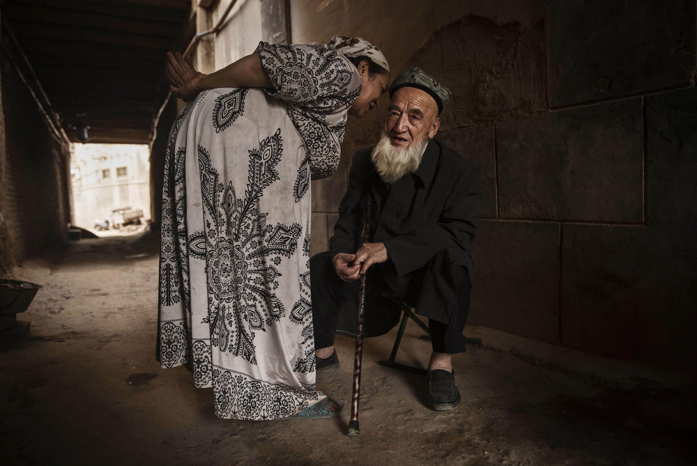 . KASHGAR, CHINA - JULY 28:  An elderly Uyghur man who said he was 100 years old listens to his wife as they sit in an alleyway before breaking their fast before the Eid holiday  on July 28, 2014 in old Kashgar, Xinjiang Province, China. Nearly 100 people have been killed in unrest in the restive Xinjiang Province in the last week in what authorities say is terrorism but advocacy groups claim is a result of a government crackdown to silence opposition to its policies. China\'s Muslim Uyghur ethnic group faces cultural and religious restrictions by the Chinese government. Beijing says it is investing heavily in the Xinjiang region but Uyghurs are increasingly dissatisfied with the influx of Han Chinese and uneven economic development.  (Photo by Kevin Frayer/Getty Images)