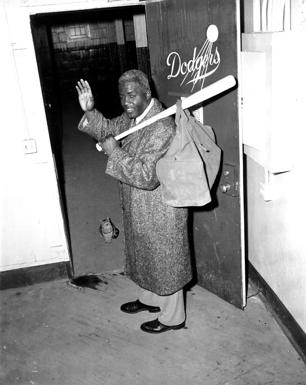 . Jackie Robinson, who retired after a 10-year career, waves as he leaves the clubhouse after collecting his belongings at Ebbets Field in Brooklyn, N.Y., on Jan. 7, 1957.  Robinson, 38, became the first black baseball player in the modern major leagues when he joined the Brooklyn Dodgers in 1947.  (AP Photo/Jacob Harris)