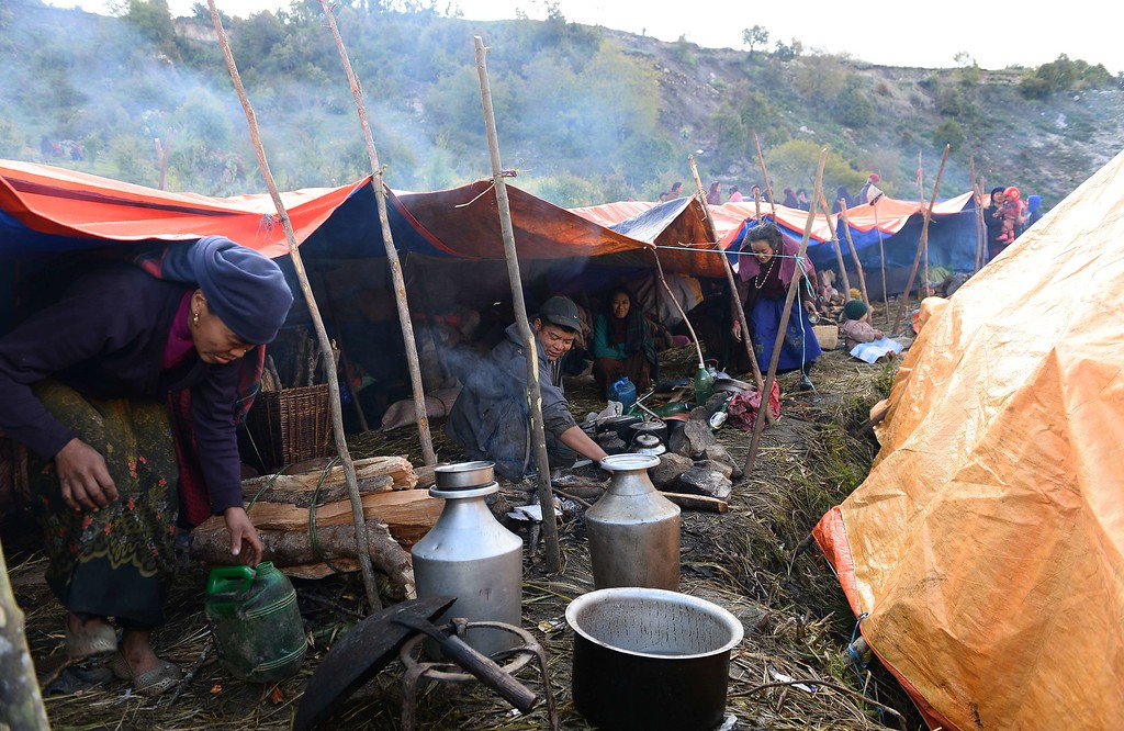 . A Nepalese man cooks food outside makeshift tents at Laprak village, in northern-central Gorkha district on April 30, 2015.  The UN launched an appeal for Nepalese quake survivors in dire need of shelter, food and medical care April 30 as anger boiled at the government\'s inability to cope with a disaster that has killed more than 5,000 people.  AFP PHOTO / SAJJAD  HUSSAIN/AFP/Getty Images