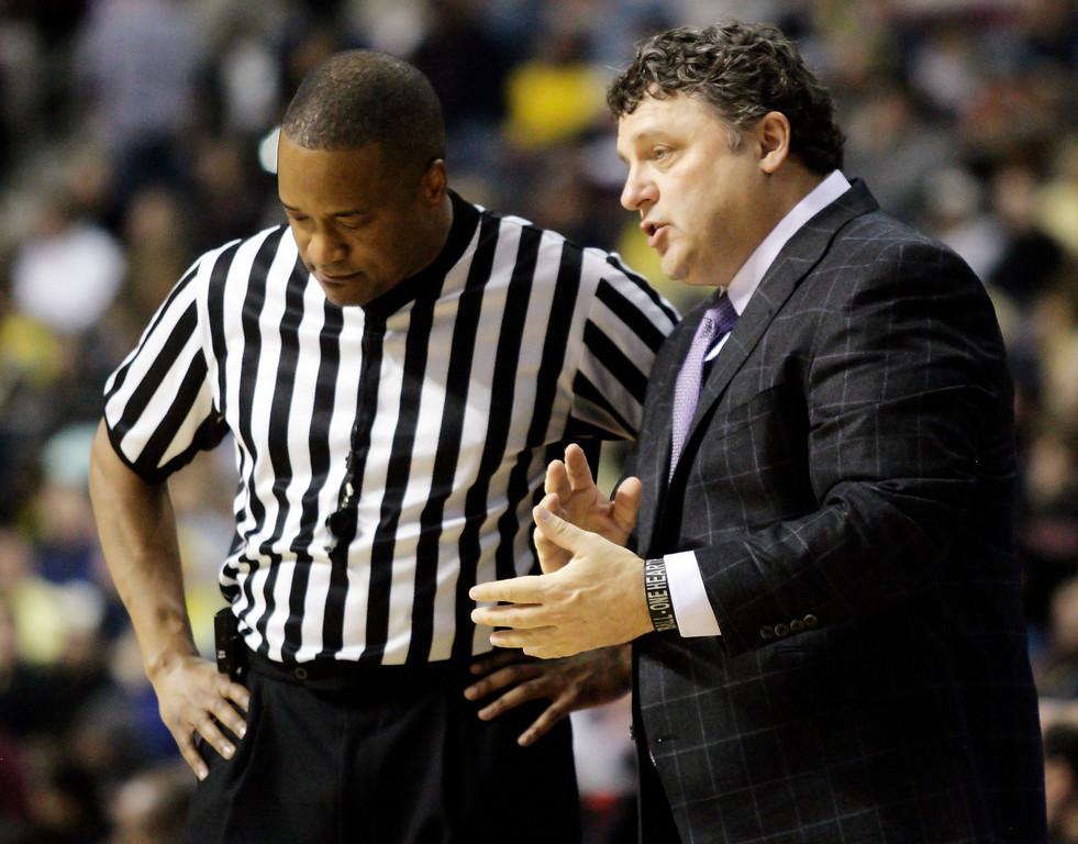 . Oakland coach Greg Kampe, right, talks with official Earl Walton in the first half of an NCAA college basketball game against Michigan, Saturday, Dec. 10, 2011, in Auburn Hills, Mich. Michigan won 90-80. (AP Photo/Duane Burleson)