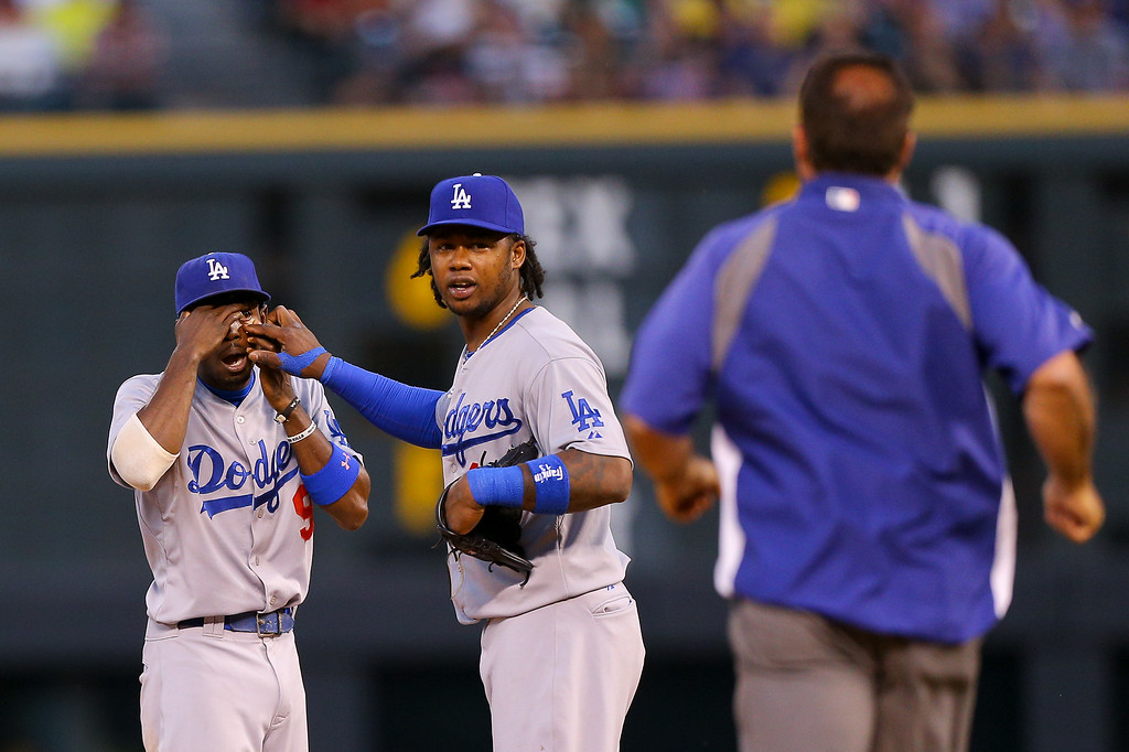 . Second baseman Dee Gordon #9 of the Los Angeles Dodgers gets some help from shortstop Hanley Ramirez #13 before the medical staff arrives after getting something stuck in his eye during a game against the Colorado Rockies at Coors Field on July 3, 2014 in Denver, Colorado. The Dodgers defeated the Rockies 3-2. (Photo by Justin Edmonds/Getty Images)