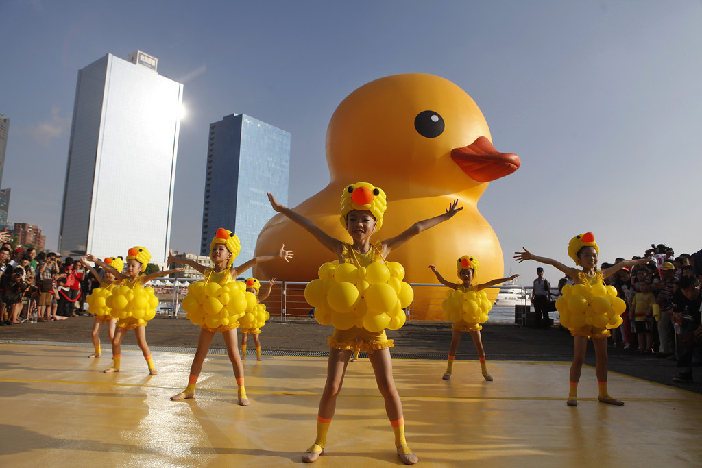 . Girls dress as ducks as people gather to see a giant Rubber Duck by Dutch conceptual artist Florentijin Hofman at Glory Pier on September 19, 2013 in Kaohsiung, Taiwan. The \'Rubber\' Duck,\' is traveling the world and will stop in Kaohsiung from September 19 to October 20.  (Photo by Ashley Pon/Getty Images)