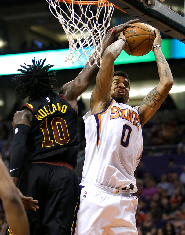 . Cleveland Cavaliers guard John Holland (10) blocks the shot of Phoenix Suns forward Marquese Chriss in the second half of an NBA basketball game, Tuesday, March 13, 2018, in Phoenix. The Cavaliers defeated the Suns 129-107. (AP Photo/Rick Scuteri)