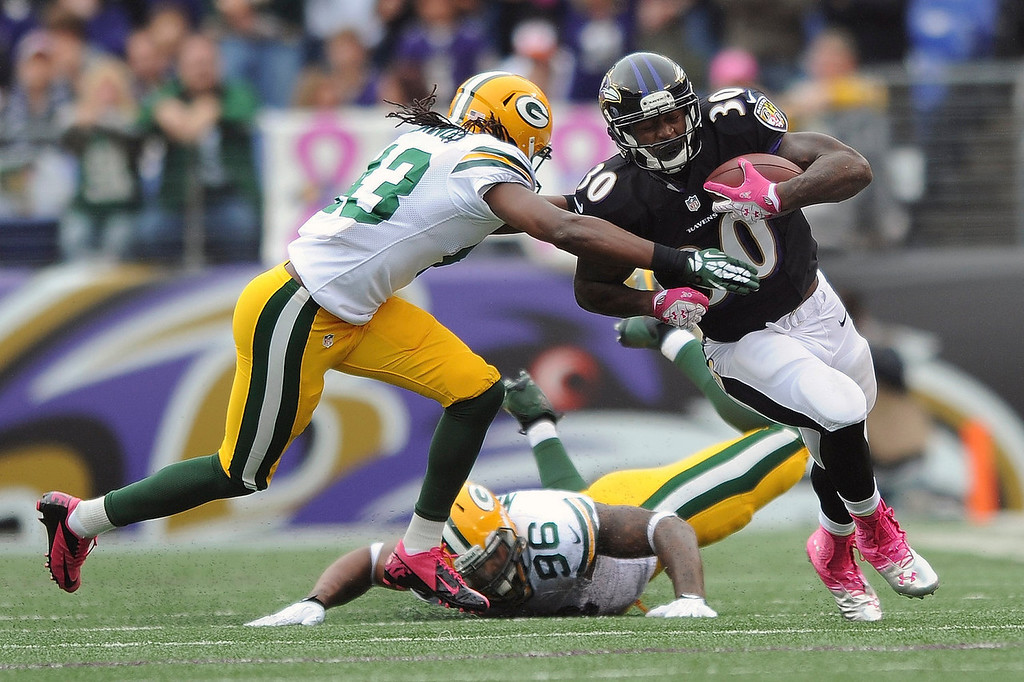 . Baltimore Ravens running back Bernard Pierce (30) is tackled by Green Bay Packers free safety M.D. Jennings as defensive end Mike Neal (96) lies on the ground during the first half of an NFL football game in Baltimore, Sunday, Oct. 13, 2013. (AP Photo/Gail Burton)