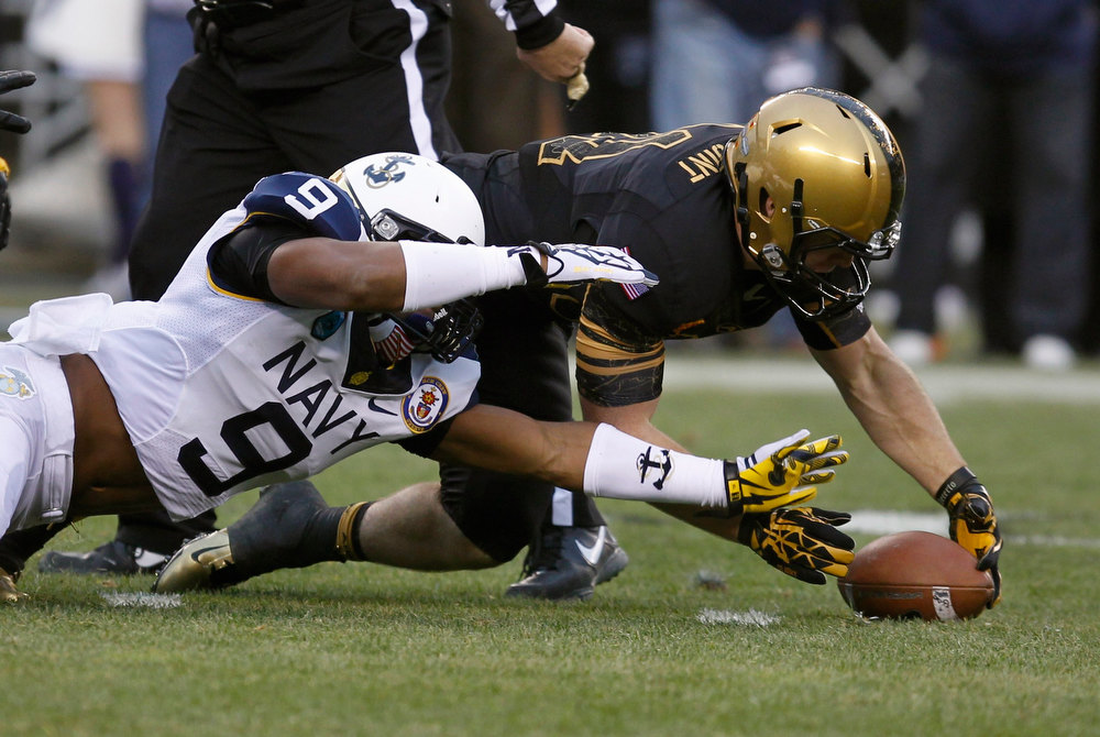 . Army receiver Patrick Laird recovers a fumble under pressure from Navy defender Tra\'Ves Bush (9) during the first quarter of the Army versus Navy NCAA football game in Philadelphia, Pennsylvania, December 8, 2012. REUTERS/Tim Shaffer