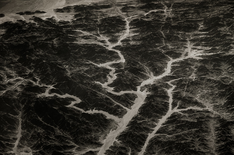 Black and white view from plane. Rivers winding through valleys in the mountains of South East Iran, Saravan 27.725992, 62.582951 (Post work to increase contrast and clarity to compensate for atmospheric haze).
