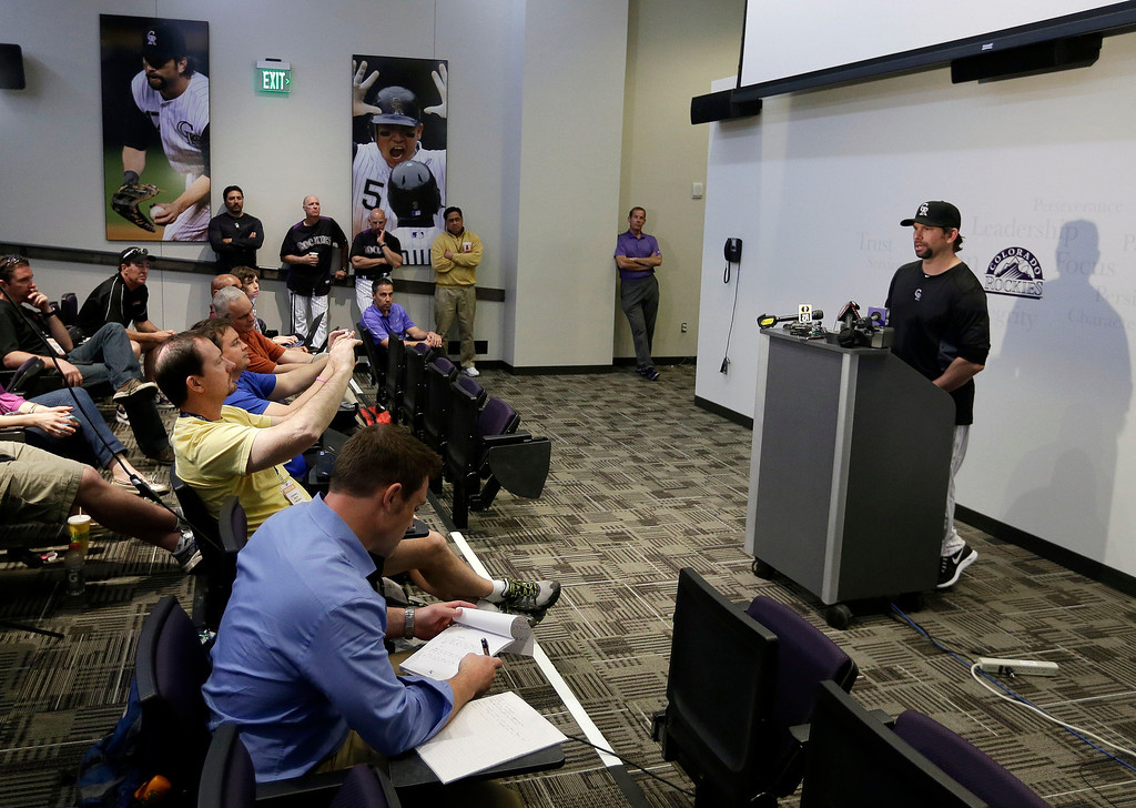 . Colorado Rockies\' Todd Helton, right, responds to a question during a news conference following a spring training baseball workout on Sunday, Feb. 17, 2013, in Scottsdale, Ariz. (AP Photo/Darron Cummings)