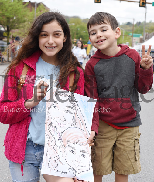 Harold Aughton/Butler Eagle: Adam Walmsley of Cabot drew caricatures of first cousins, Isabella Morales, 11, of Lyndora and Dekland Coburn, 6, of Butler, Saturday afternoon, at the Butler County Recovery and Resource Block Party.