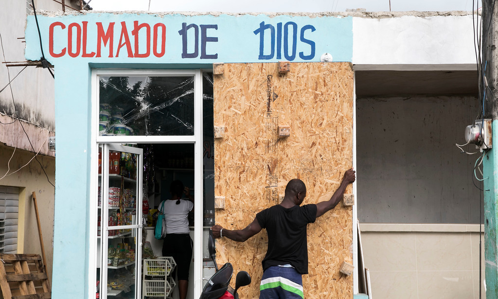 . A man covers a bodega\'s windows before the arrival of Hurricane Irma in Las Terrenas, Dominican Republic, Wednesday, Sept. 6, 2017. Dominicans are getting ready for the arrival of Hurricane Irma after battering Puerto Rico with heavy rain and powerful winds, leaving more than 600,000 people without power as authorities struggle to get aid to small Caribbean islands already devastated by the historic storm.(AP Photo/Tatiana Fernandez)
