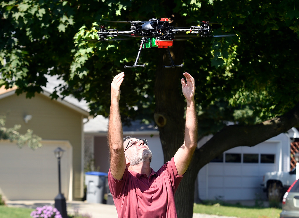 . LONGMONT, CO - AUGUST 9: Dan Staley, of Arbor Drones, catches the drone to avoid any damage in the landing. Arbor Drone LLC and Spectrabotics LLC,  collected data using drone flights over northwest Longmont on August 9, 2018, to study and monitor trees affected by Emerald Ash Borer (EAB).  Longmont will be one of the last EAB detection flights for 2018 for the team. Drone flights in urban areas to study tree pests have never been conducted at this scale. (Photo by Cliff Grassmick/Staff Photographer)