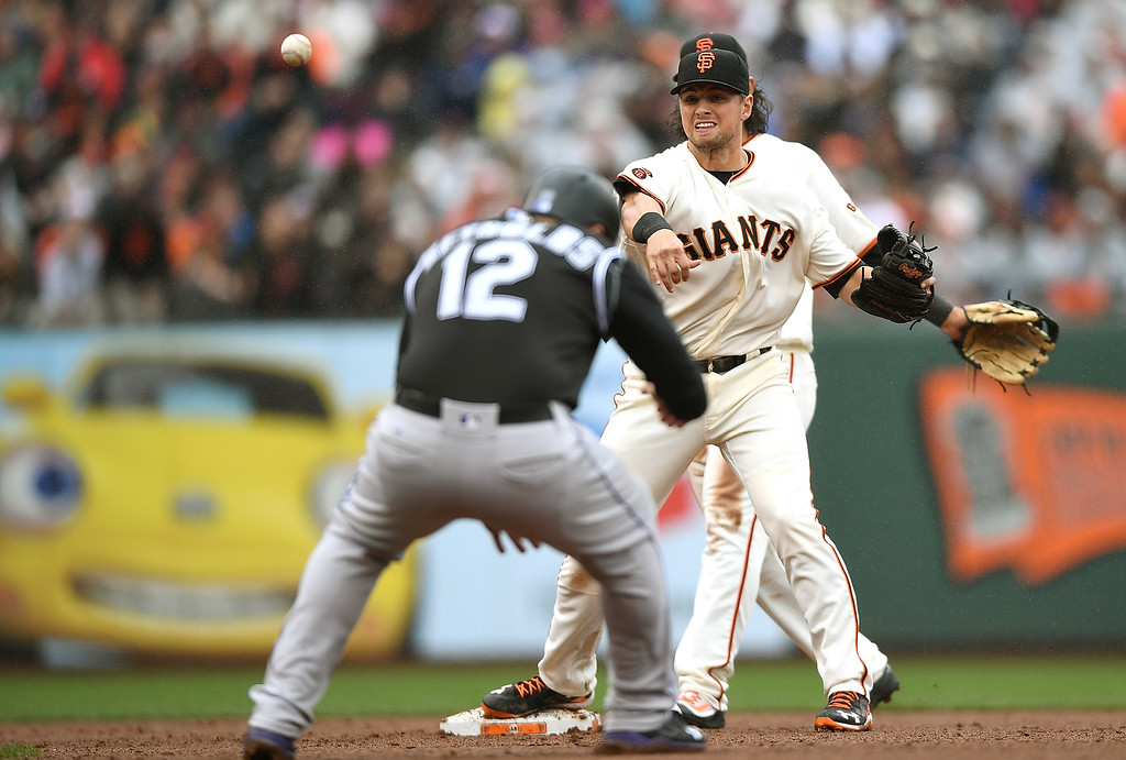 . SAN FRANCISCO, CA - MAY 07:  Joe Panik #12 of the San Francisco Giants completes the double-play over the top of Mark Reynolds #12 of the Colorado Rockies in the top of the fifth inning at AT&T Park on May 7, 2016 in San Francisco, California.  (Photo by Thearon W. Henderson/Getty Images)