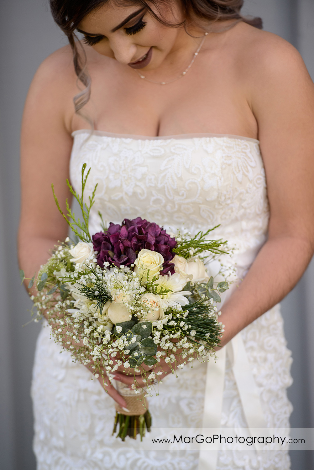 bride looking at her bouquet at Pleasant Hill City Hall
