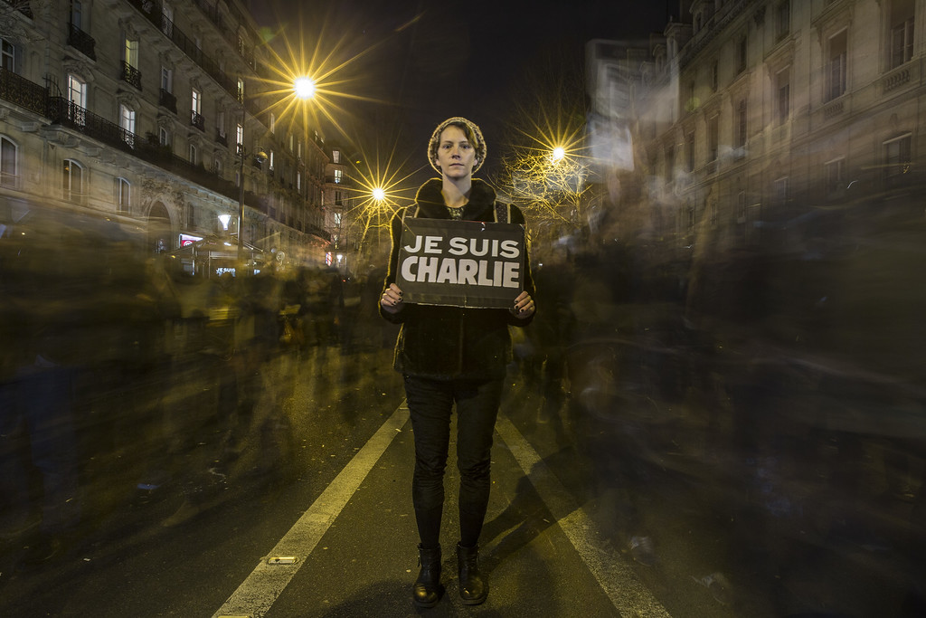 . PARIS, FRANCE - JANUARY 11: A woman pauses for a picture during a mass unity rally following the recent Paris terrorist attacks on January 11, 2015 in Paris, France. An estimated one million people have converged in central Paris for the Unity March joining in solidarity with the 17 victims of this week\'s terrorist attacks in the country. French President Francois Hollande led the march and was joined by world leaders in a sign of unity. The terrorist atrocities started on Wednesday with the attack on the French satirical magazine Charlie Hebdo, killing 12, and ended on Friday with sieges at a printing company in Dammartin en Goele and a Kosher supermarket in Paris with four hostages and three suspects being killed. A fourth suspect, Hayat Boumeddiene, 26, escaped and is wanted in connection with the murder of a policewoman.  (Photo by Dan Kitwood/Getty Images) *** BESTPIX ***
