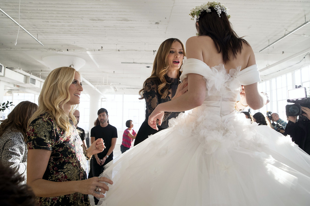 . In this Wednesday, Oct. 5, 2016 photo, designers Keren Craig, left, and Georgina Chapman put final adjustments on a gown ahead of the Marchesa bridal collection show during bridal fashion week in New York.  (AP Photo/Mary Altaffer)