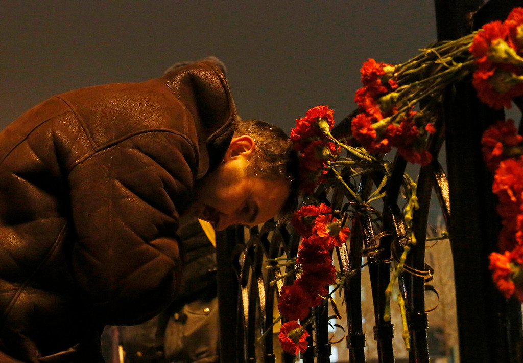 . A  man grieves outside the Volgograd main railway station in Volgograd, Russia early Monday, Dec. 30, 2013. A bomb blast tore through a trollybus in the city of Volgograd on Monday morning, killing at least 14 people a day after a suicide bombing that killed at least 17 at the city\'s main railway station. Volgograd is about 650 kilometers (400 miles) northeast of Sochi, where the Olympics are to be held. (AP Photo/Denis Tyrin)