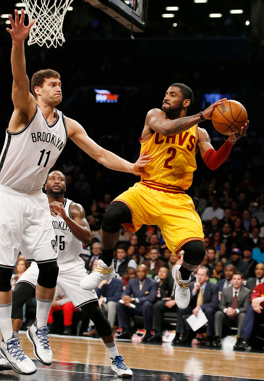 . Brooklyn Nets center Brook Lopez (11) defends Cleveland Cavaliers guard Kyrie Irving (2) who looks to pass in the first half of an NBA basketball game, Thursday, March 24, 2016, in New York. (AP Photo/Kathy Willens)