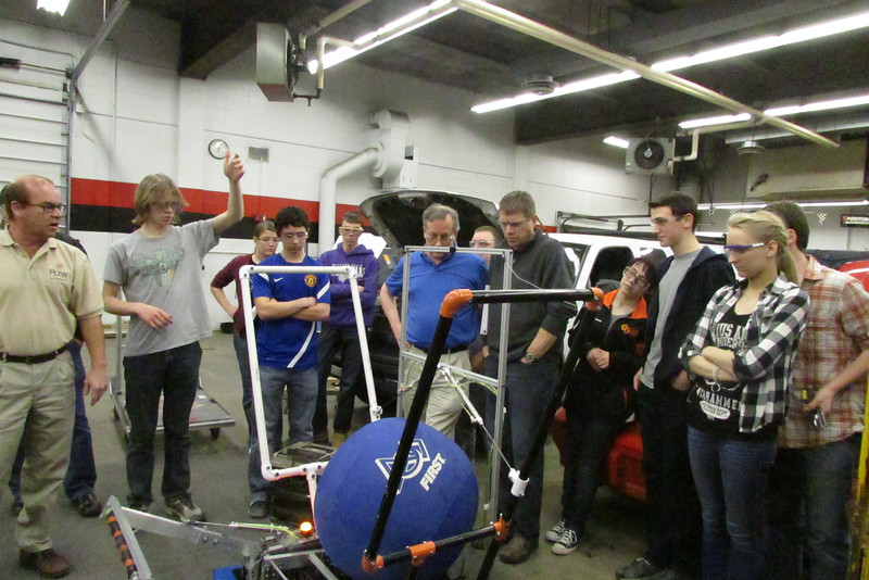 Many members of the team gather to see the second robot shoot in the autoshop