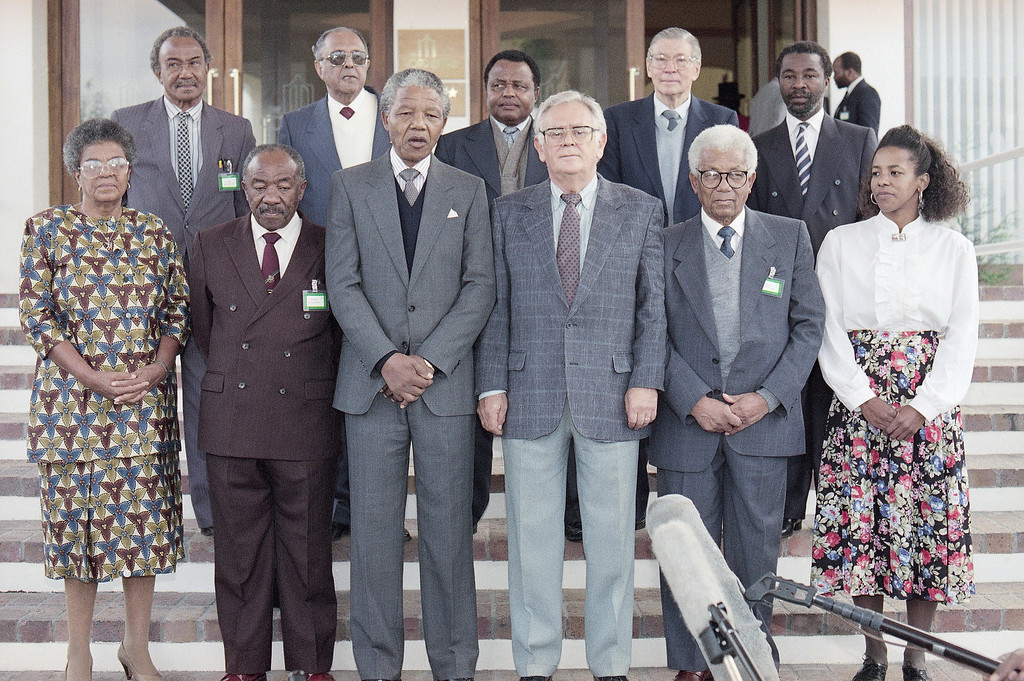 . The African National Congress delegation poses on Wednesday, May 2, 1990 in Somerset West, South Africa prior to talk with the South African Government. They are: back row from left; Archie Cumede, Ahmed Kathrada, Joe Modise, Beyers Naude, Thabo Mbeki. Front from left, Ruth Mompati, Alfred Nzo (ANC GenSec),. Nelson Mandela (deputy President), Joe Slove (SACP secretary general), Walter Sisulu and Cheryl Carolus. (AP Photo/Adil Bradlow)