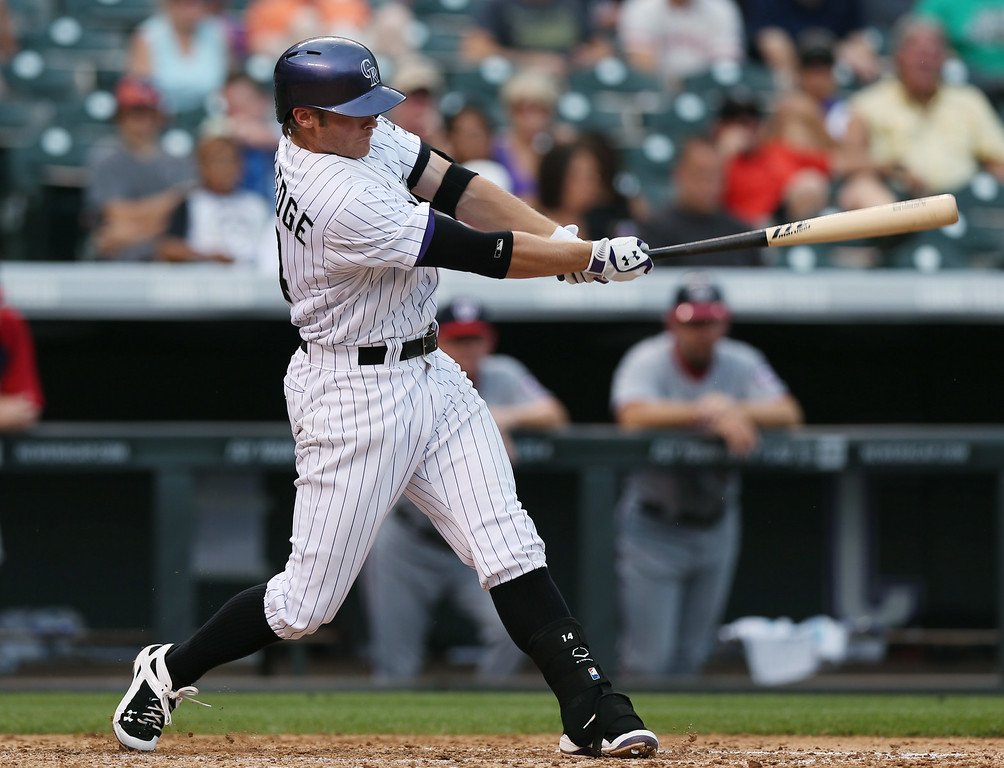 . Colorado Rockies\' Josh Rutledge follows through with swing after connecting for double against the Washington Nationals in the fifth inning of a baseball game in Denver on Wednesday, July 23, 2014. (AP Photo)