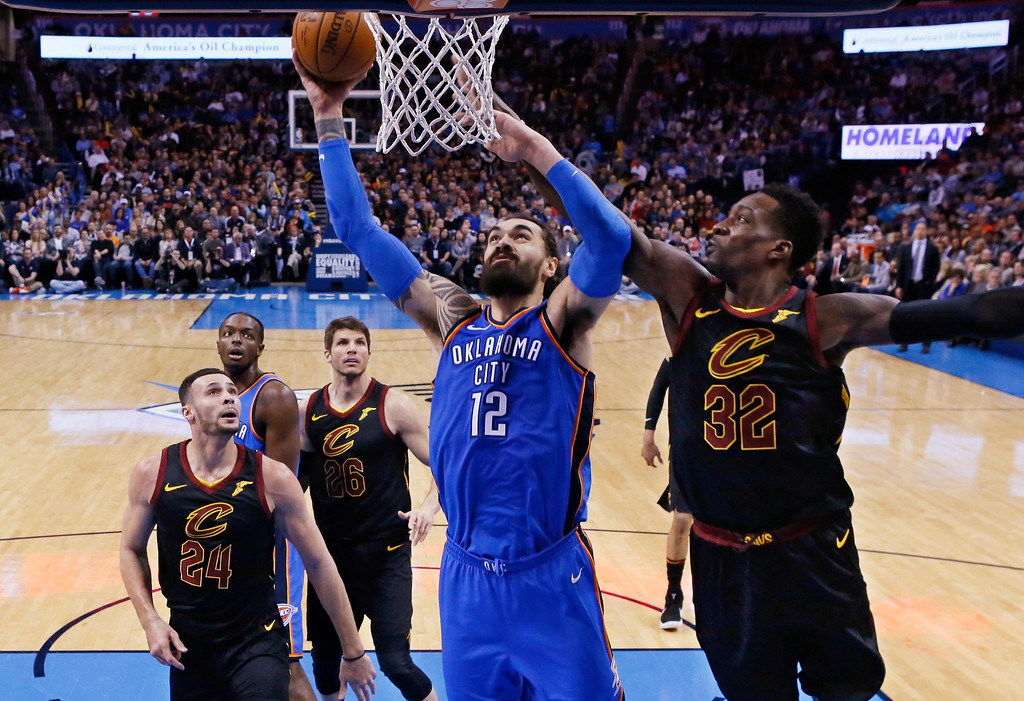. Oklahoma City Thunder center Steven Adams (12) shoots between Cleveland Cavaliers forward Larry Nance Jr. (24) and forward Jeff Green (32) during the first half of an NBA basketball game in Oklahoma City, Tuesday, Feb. 13, 2018. (AP Photo/Sue Ogrocki)