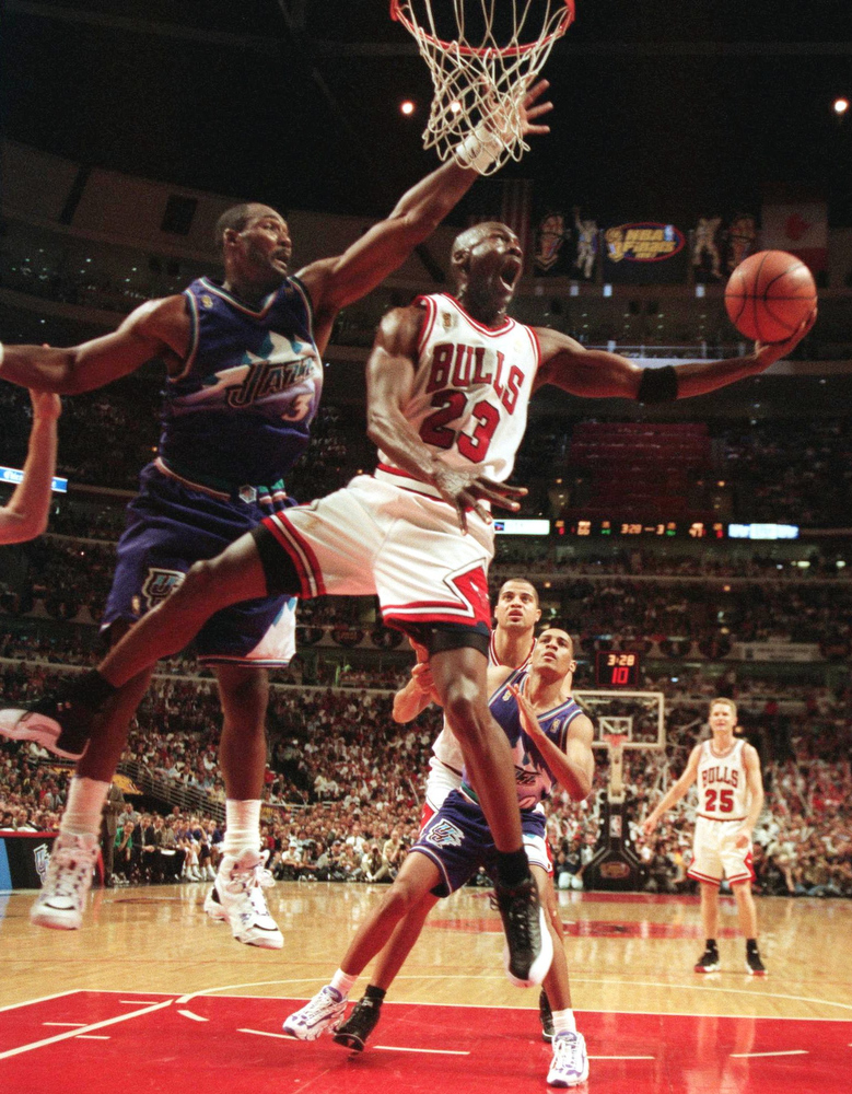 Description of . The Chicago Bulls' Michael Jordan (23) goes up and under Utah Jazz forward Karl Malone, left, as he drives to the hoop during the third quarter of  Game 2  in the NBA Finals Wednesday, June 4, 1997, in Chicago.  (AP Photo/Beth A. Keiser)