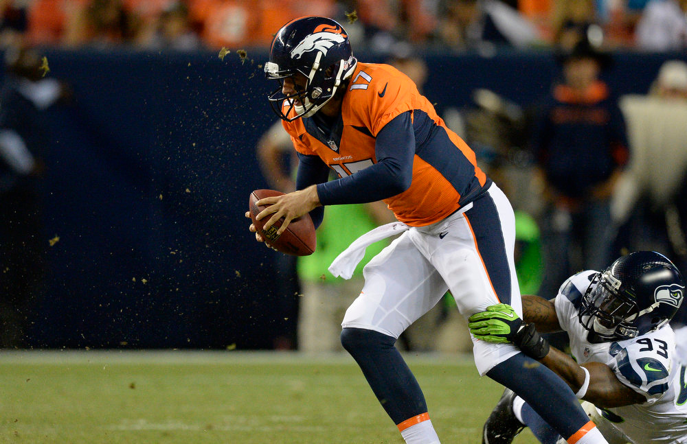 . Denver Broncos quarterback Brock Osweiler (17) escapes the grip of Seattle Seahawks defensive end O\'Brien Schofield (93) during the third quarter August 7, 2014 at Sports Authority Field at Mile High Stadium.  (Photo by John Leyba/The Denver Post)