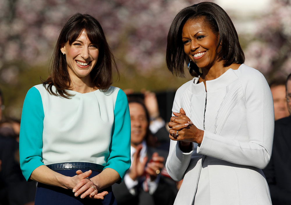 Description of . First Lady Michelle Obama, right, and Samantha Cameron, wife of David Cameron, smile during an official state arrival ceremony on the South Lawn of the White House in Washington, D.C., U.S., on Wednesday, March 14, 2012. Obama welcomed Cameron to the White House to start off an official visit combining ceremony with discussions on such critical issues as Afghanistan and the global economy. Photographer: Chip Somodevilla/Pool via Bloomberg