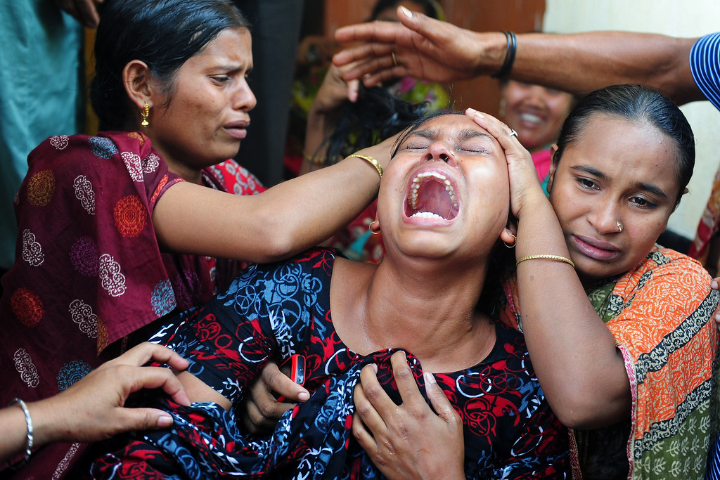 . Relatives react after identifying the body of a loved one killed in a building collapse in Savar, on the outskirts of Dhaka, on May 3, 2013. The death toll passed 500 as the country\'s prime minister said Western retailers had to share some of the blame for the tragedy.  MUNIR UZ ZAMAN/AFP/Getty Images