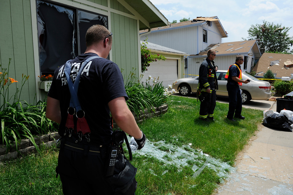 . An Arvada fire fighter walks past broken glass blown out from a house explosion on the 9300 block of Ingalls Street in Westminster, Colorado, Thursday afternoon June 13, 2013.  (Photo By Andy Cross/The Denver Post)