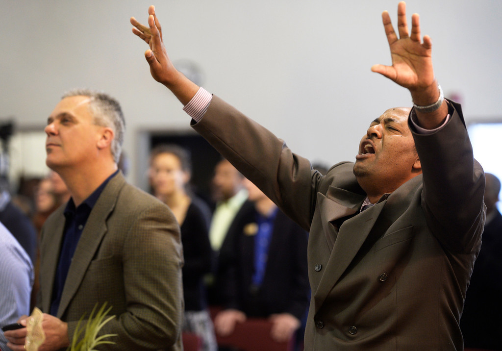 . AURORA, CO. - JANUARY 11:  Addis Kidan Evangelical Church elder, Sheleme Tur, right, prays during the church dedication service Saturday morning, January 10, 2014. (Photo By Andy Cross / The Denver Post)