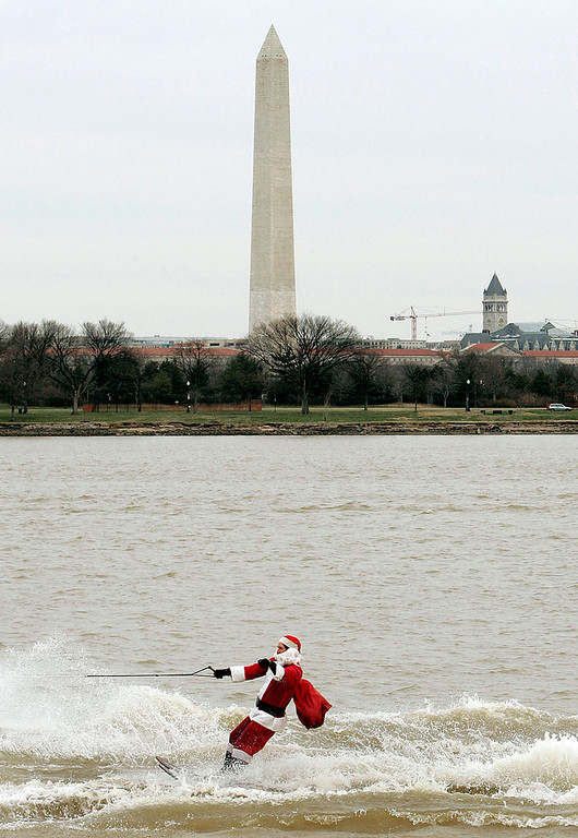 . Dressed as Santa Claus, Kerry Nistel water-skis past the Washington Monument on the frigid waters of the Potomac River December 24, 2004 in Arlington, Virginia. This is the 19th year Nistel has dressed as Santa and water-skied on Christmas Eve.  (Photo by Mark Wilson/Getty Images)