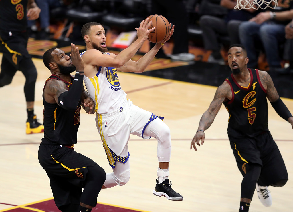 . Golden State Warriors\' Stephen Curry goes to the basket against Cleveland Cavaliers\' LeBron James, left, during the second half of Game 3 of basketball\'s NBA Finals, Wednesday, June 6, 2018, in Cleveland. (AP Photo/Carlos Osorio)