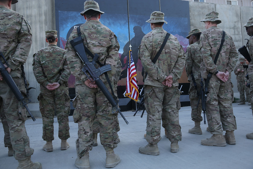 . U.S. service members stand in front of a U.S. flag during a ceremony on the thirteenth anniversary of the 9/11 terrorist attacks in front of the World Trade Center Memorial at Bagram Airfield, Afghanistan Thursday, Sept. 11, 2014. (AP Photo/Massoud Hossaini)
