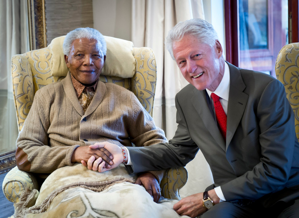 Description of . In this handout provided by the Clinton Foundation, former U.S. President Bill Clinton (R) poses with former South African President Nelson Mandela on the eve of his 94th birthday at his residence July 17, 2012 in Qunu, South Africa.  Along with his daughter Chelsea, Clinton met with Mandela for 90 minutes.  (Photo by Barbara Kinney/Clinton Foundation via Getty Images)